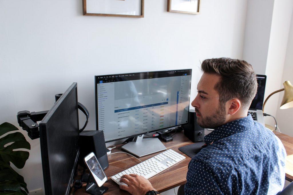 Trabajador utilizando dos pantallas de ordenador